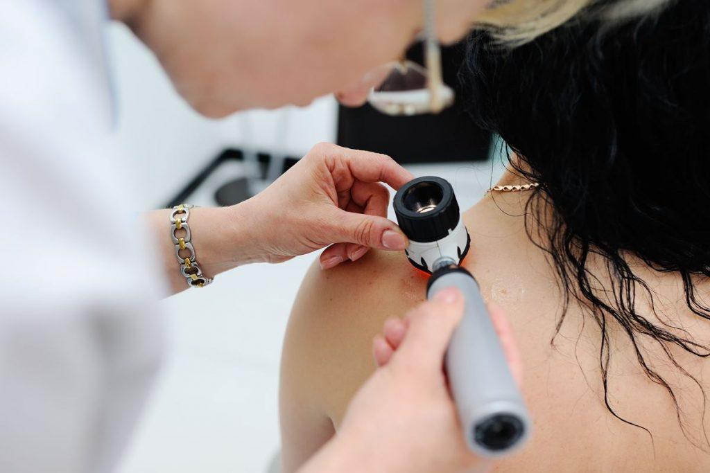 Dermatologist using a dermatoscope on a patient